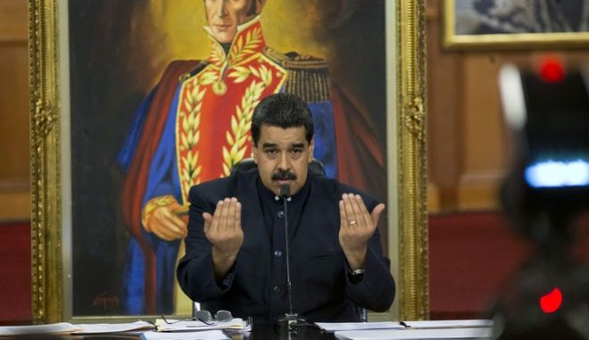 Backdropped by a painting of independence hero Simon Bolivar, Venezuela's President Nicolas Maduro speaks during a press conference at the Miraflores presidential palace, in Caracas, Venezuela, Tuesday, Oct. 17, 2017. Maduro defended the results of Sunday's gubernatorial elections and said that those who report fraud are lying.  (AP Photo/Ariana Cubillos)