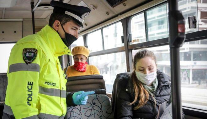 Γυναίκα με μάσκα σε λεωφορείο και αστυνομικός  (EUROKINISSI)