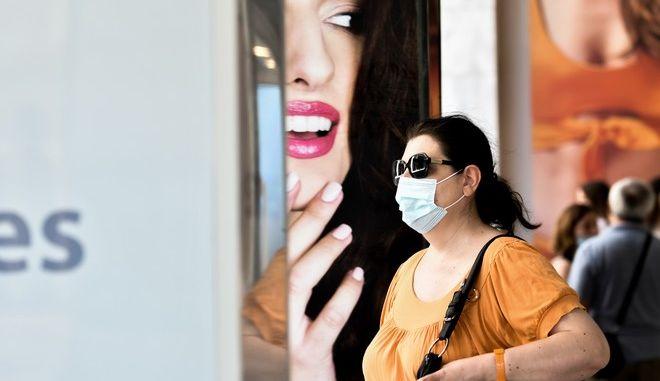 Γυναίκα με μάσκα έξω από κατάστημα.