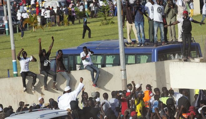 Gambian President Adama Barrow, bottom left, waves as he rides his motorcade through crowds of hundreds of thousands after arriving at Banjul airport in Gambia, Thursday Jan. 26, 2017, after flying in from Dakar, Senegal. Gambia's new president has finally arrived in the country, a week after taking the oath of office abroad amid a whirlwind political crisis. Here's a look at the tumble of events that led to Adama Barrow's return  and the exile of the country's longtime leader. (AP Photo/Jerome Delay)
