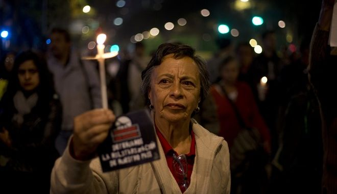 "A protester holds a candle and small sign that says in Spanish ""Security without war. Stop the militarization of our country"" during a candlelight march against a newly proposed security law in Mexico City, late Wednesday, Dec. 13, 2017.  Mexico's ruling party rammed a bill through Congress' lower house on Dec. 7 giving the military legal justification to act as police, triggering objections by those who said it would effectively militarize the country. The Senate will now take up the legislation. (AP Photo/Eduardo Verdugo)"