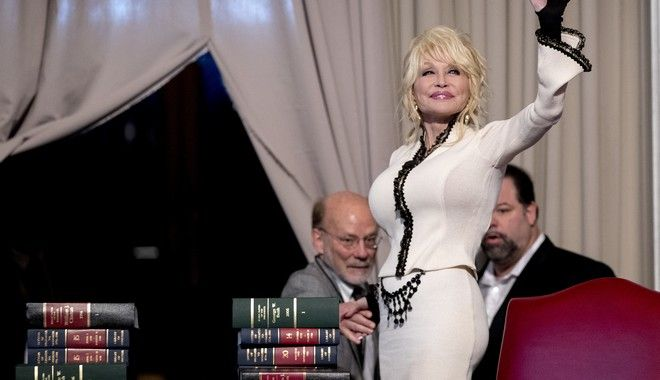 Singer-songwriter Dolly Parton waves to the audience following an event where her organization, Imagination Library, donates the 100 millionth book, Dolly Parton's