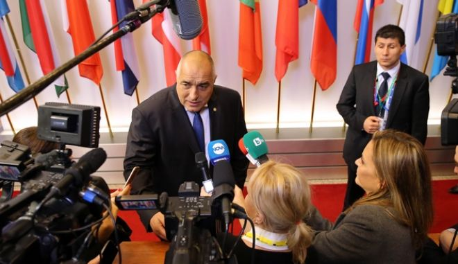 Bulgarian Prime Minister Boyko Borisov, center, speaks with the media at an EU summit in Brussels on Friday, Feb. 19, 2016. British Prime Minister David Cameron faces tough new talks with European partners after through-the-night meetings failed to make much progress on his demands for a less intrusive European Union. (AP Photo/Francois Walschaerts)