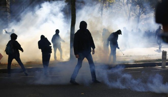 Demonstrators stand in clouds of teargas during a rally to protest President Emmanuel Macron's new pro-business labor policies in Paris, France, Thursday, Sept. 21, 2017. President Emmanuel Macron's presidency is facing its second big public test, as unions hold nationwide protests against changes to labor laws that they fear corrode hard-fought job security. (AP Photo/Thibault Camus)