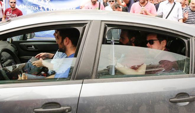 """Το αυτοκίνητο της ασφάλειας που οδηγεί στον Εισαγγελέα τον Αρτέμη Σώρρα την που υπάρχουν Συγκεντρωμένοι οπαδοί του αρχηγού των 'Ελληνων Συνελευσις"""" έξω από τα δικαστήρια της Ευελπίδων"""