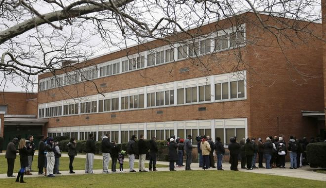 FILE - In this Jan. 15, 2013 file photo, family members wait in line to pick up students after a lockdown was lifted at Elmont Memorial High School in Elmont, N.Y. The Long Island school returned to normal after a report of a gun prompted an hours-long lockdown. The push to have an armed police officer at every school in New York state is being renewed in the wake of the Florida high school shooting that left over a dozen dead. (AP Photo/Seth Wenig, File)