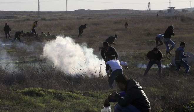 Palestinian protesters run for cover from teargas fired by Israeli soldiers during clashes on the Israeli border following a protest against U.S. President Donald Trump's decision to recognize Jerusalem as the capital of Israel, east of Gaza City, Friday, Dec. 8, 2017. (AP Photo/Adel Hana)
