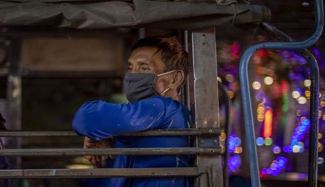 Μετανάστης κατασκευαστής που φοράει μάσκα προσώπου ταξιδεύει σε φορτηγό Μπανγκόκ της Ταϊλάνδης