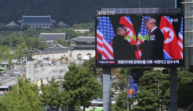"""A TV screen shows a photo of North Korean leader Kim Jong Un, left, and U.S. President Donald Trump to advertise upcoming Seoul Defense Dialogue in Seoul, South Korea, Wednesday, Sept. 5, 2018. A South Korean presidential delegation met with North Korean officials Wednesday for talks to arrange a summit planned later this month and help rescue faltering nuclear diplomacy between Washington and Pyongyang. The sign read: """"World Peace."""" (AP Photo/Ahn Young-joon)"""
