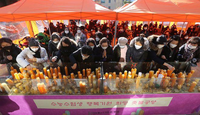Οι γονείς τοποθετούν κεριά για να ευχηθούν την επιτυχία των παιδιών τους στις εξετάσεις, στο βουδιστικό ναό Jogyesa στη Σεούλ, Νότια Κορέα, 3 Δεκεμβρίου 2020.