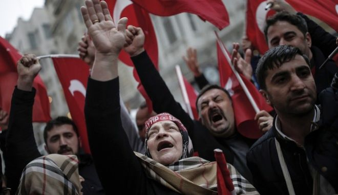 "A group of Turks protest outside the Dutch consulate in Istanbul, Sunday, March 12, 2017. Turkish President Recep Tayyip Erdogan says he appropriately accused the Dutch government of ""Nazism and fascism,"" saying only those types of regimes would bar foreign ministers from traveling within their countries. Erdogan also said during a live televised address on Sunday that the Netherlands would ""pay the price"" for sacrificing its ties with a NATO ally to upcoming elections there. (AP Photo/ Emrah Gurel)"