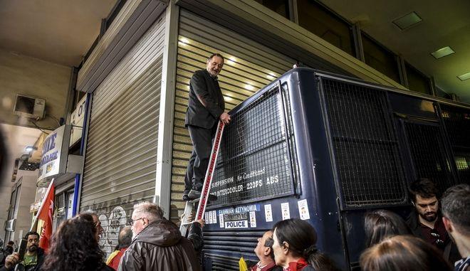 Μέλη της Λαϊκής Ενότητας και άλλων κινημάτων έχουν συγκεντρωθεί έξω από συμβολαιογραφείο στην οδό Πανεπιστημίου , διαμαρτυρόμενοι για την διεξαγωγή ηλεκτρονικών πλειστηριασμών.