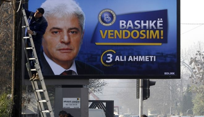 In this picture taken Nov. 21, 2016, a man works on a pole, beside an electoral poster of Ali Ahmeti, head of the ethnic Albanian party DUI and a partner in the country's ruling coalition, displayed on a street in Skopje. Macedonia heads to early general elections this weekend after the most divisive and vicious political campaign in the country's brief history of independence, following a nearly two-year political crisis that roiled the government and threatened the country's ambitions of joining NATO and the European Union. (AP Photo/Boris Grdanoski)
