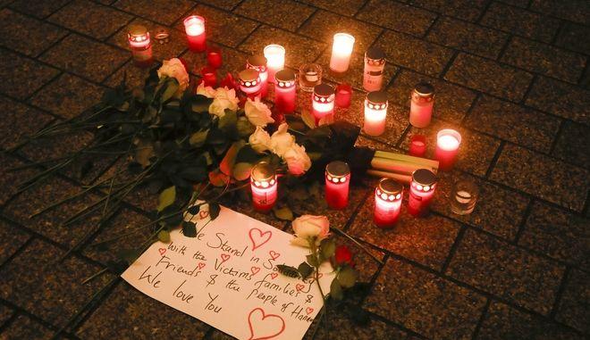 Κηροπήγια και λουλούδια τοποθετημένα στο πάτωμα κατά τη διάρκεια επαγρύπνησης για θύματα της τραγωδίας στην κεντρική γερμανική πόλη Hanau