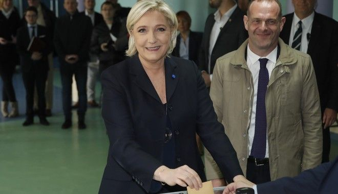 CORRECTS NAME OF THE MAN - Far-right leader and candidate for the 2017 French presidential election Marine Le Pen casts her vote for the first-round presidential election, while National Front Henin-Beaumont's mayor Steeve Briois, right, looks on, in Henin-Beaumont, northern France, Sunday, April 23, 2017. French voters are casting ballots for their next president in an unusually close first-round election Sunday, after a campaign dominated by concerns about jobs and immigration and clouded by security fears following a recent attack on police guarding the Champs-Elysees in Paris. (AP Photo/Frank Augstein)