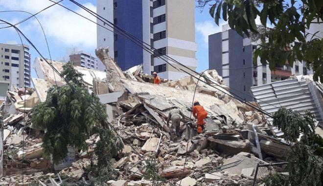 Πυροσβέστες αναζητούν επιζώντες στα ερείπια του κτιρίου.