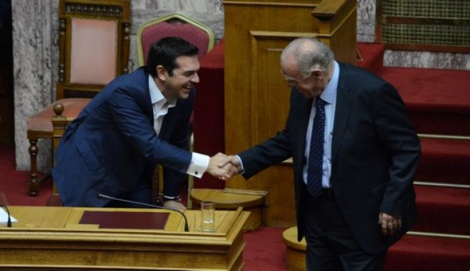 "ATHENS, GREECE - 2015/10/07: Greek Prime Minister Alexis Tsipras (left) greets Vassilis Leventis (right) during the "" Vote for Confidence at Parliament"" where 155 voted yes and 144 voted no,  while only one legislator was absent. (Photo by George Panagakis/Pacific Press/LightRocket via Getty Images)"
