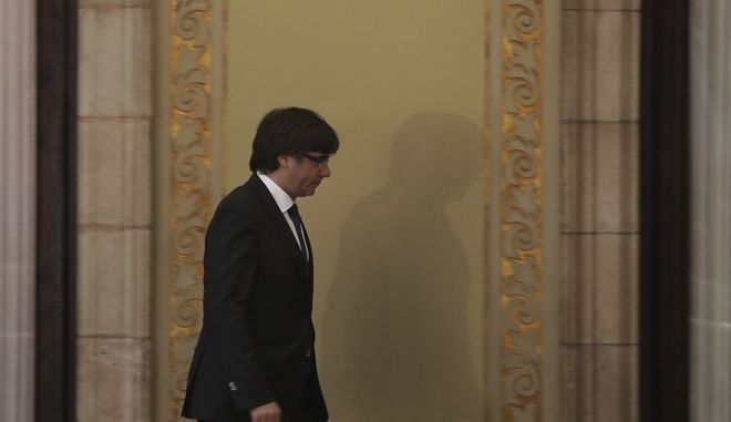 Catalan President Carles Puigdemont walks after his arrival inside the Catalan parliament in Barcelona, Spain, Friday, Oct. 27, 2017. Catalonia's parliament on Friday will resume debating its response to the Spanish government's plans to strip away its regional powers to halt it pushing toward independence.(AP Photo/ Emilio Morenatti)