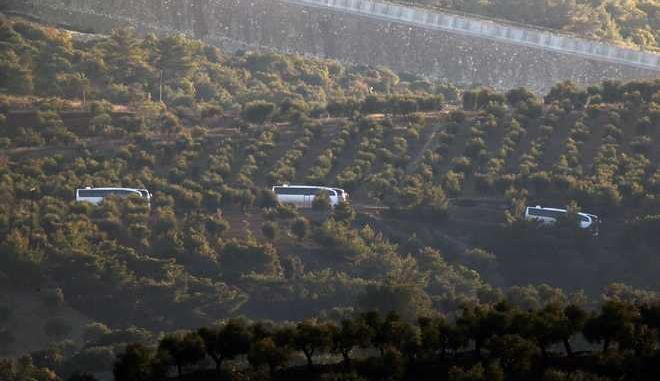 """A convoy of buses believed to be carrying Syrian opposition fighters, travels along the border with Syrias as see from the outskirts of the border town of Kilis, Turkey, Saturday, Jan. 20, 2018. Turkish jets have begun an aerial offensive, codenamed operation """"Olive Branch"""", against the Syrian Kurdish-held enclave of Afrin, in northwest Syria . A military statement says the operation launched Saturday aims to protect Turkey's borders, """"neutralize"""" Syrian Kurdish fighters in the enclave and to save the local population from their """"pressure and oppression."""" (AP Photo/Lefteris Pitarakis)"""
