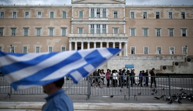 A man walks in front of Greek Parliament as carries a Greek flag in Athens, Greece on December 05, 2014. /                5  2014.