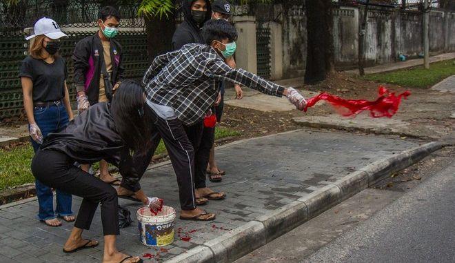 Διαδηλωτές πετούν κόκκινες μπογιές στο δρόμο