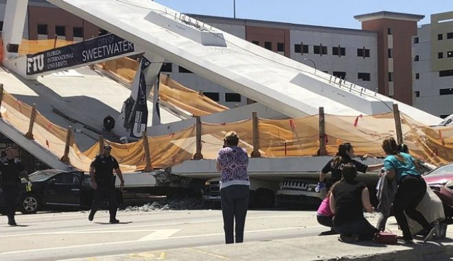 Emergency personnel respond to people near a collapsed pedestrian bridge at Florida International University on Thursday, March 15, 2018, in the Miami area. The brand-new pedestrian bridge collapsed onto a highway crushing multiple vehicles and killing several people. (WTVJ NBC6 via AP)