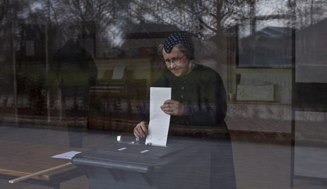 An elderly woman casts her ballot for the Dutch general elections at a polling station set up in a school in Staphorst, Netherlands, Wednesday, March 15, 2017. Amid unprecedented international attention, the Dutch go to the polls Wednesday in a parliamentary election that is seen as a bellwether for the future of populism in a year of crucial votes in Europe. (AP Photo/Muhammed Muheisen)