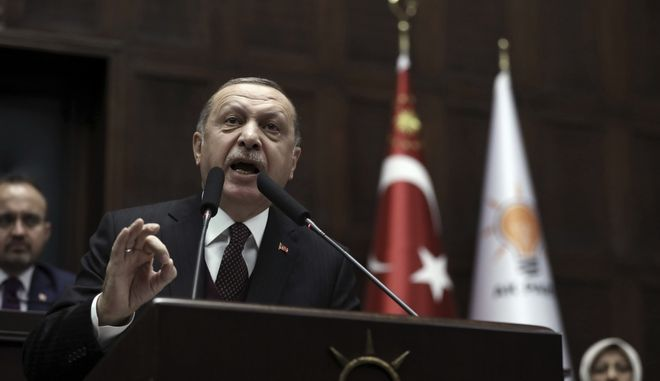 Turkey's President and leader of ruling Justice and Development Party Recep Tayyip Erdogan addresses his supporters and lawmakers at the parliament in Ankara, Turkey, Tuesday, Jan. 9, 2018. (AP Photo/Burhan Ozbilici)