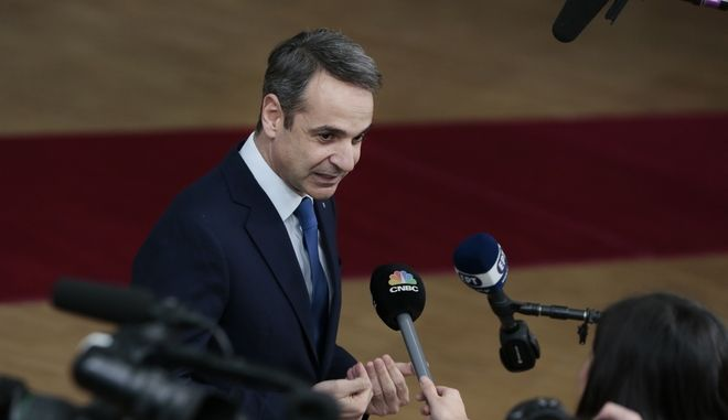 Greek Prime Minister Kyriakos Mitsotakis speaks with the media as he arrives for an EU summit at the European Council building in Brussels, Thursday, Feb. 20, 2020. After almost two years of sparring, the EU will be discussing the bloc's budget to work out Europe's spending plans for the next seven years. (AP Photo/Virginia Mayo)