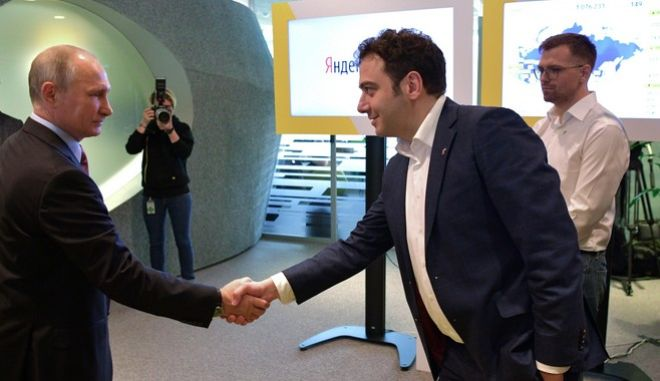 Russian President Vladimir Putin, left, shakes hands with Tigran Khudaverdyan, manager of Yandex.Taxi project, as he visits Russia's largest internet search engine Yandex headquarters in Moscow, Russia, Thursday, Sept. 21, 2017. (Alexei Druzhinin, Sputnik, Kremlin Pool Photo via AP)