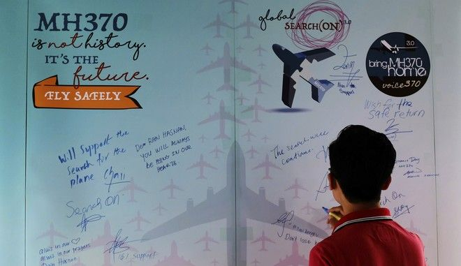 A man writes a condolence message during the Day of Remembrance for MH370 event in Kuala Lumpur, Malaysia on Saturday, March 4, 2017. After three years, the hunt for Malaysia Airlines Flight 370 ended in futility and frustration on Tuesday, Jan. 17, 2017, as crews completed their deep-sea search of a desolate stretch of the Indian Ocean without finding a single trace of the plane. (AP Photo/Daniel Chan)
