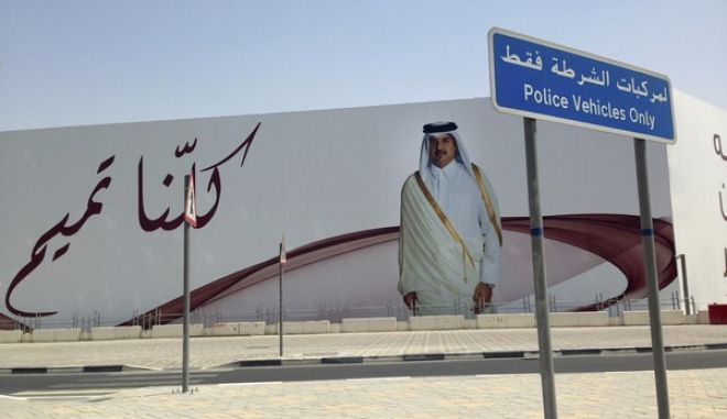 "FILE- In this Monday, July 3, 2017 file photo, an image of Qatar's emir, Sheikh Tamim bin Hamad Al Thani, graces a billboard featuring the slogan ""We are all Tamim"" in Doha, Qatar. Qatar's answer to a list of demands from four countries lined up against it may be shrouded in secrecy, but the message it delivered this week was clear enough: it is not about to roll over. (AP Photo/Maggie Hyde, File)"