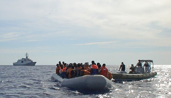 """In this handout picture released by the Italian navy on October 31, 2013 migrants sit in a boat during a rescue operation off the coast of Sicily on October 30, 2013. About 317 migrants, who were travelling in two separate boats which were damaged, were rescued in the operation called Mare Nostrum. = RESTRICTED TO EDITORIAL USE - MANDATORY CREDIT """"AFP PHOTO / MARINA MILITARE"""" - NO MARKETING NO ADVERTISING CAMPAIGNS - DISTRIBUTED AS A SERVICE TO CLIENTS ="""