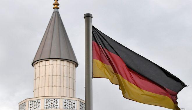Γερμανική σημαία κυματίζει μπροστά από έναν μιναρέ τζαμιού