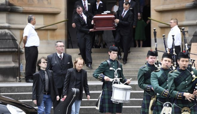 Angus Young, the brother of Malcolm Young, front center, carries a guitar as he leads the casket of his brother Malcolm Young, AC/DC co-founder and guitarist, from St. Mary's Cathedral in Sydney, Tuesday, Nov. 28, 2017. Malcolm along with his brother Angus Young founded the iconic rock group AC/DC. (Dean Lewins/AAP via AP)