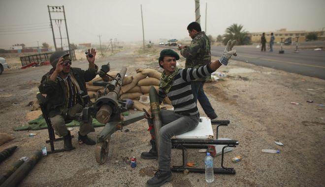 Στρατιώτες και εθελοντές της Λιβύης κάθονται με όπλα στα περίχωρα  πόλης Μπρέγκα