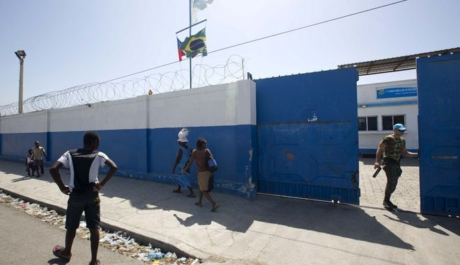 In this Aug. 16, 2016 photo, a Brazilian U.N. peacekeeper opens a gate at the U.N. base in the Cite Soleil slum of Port-au-Prince, Haiti. According to an AP investigation, some 150 allegations of abuse and exploitation were reported in Haiti between 2004 and 2016. The allegations involved U.N. peacekeepers and other personnel. Alleged victimizers came from Bangladesh, Brazil, Jordan, Nigeria, Pakistan, Uruguay and Sri Lanka, according to U.N. data and interviews. More countries may have been involved, but the United Nations only started disclosing alleged perpetrators nationalities after 2015. (AP Photo/Dieu Nalio Chery)