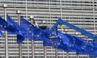 A worker on a lift adjusts the EU flags in front of EU headquarters in Brussels on Wednesday, June 22, 2016. Voters in the United Kingdom are taking part in a referendum that will decide whether Britain remains part of the European Union or leaves the 28-nation bloc. (AP Photo/Virginia Mayo)