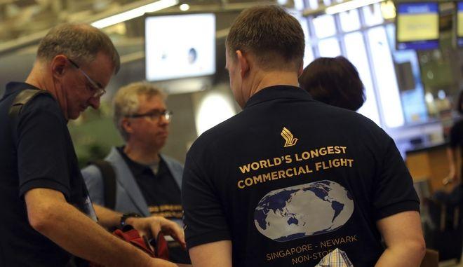 Επιβάτες της μεγαλύτερης χωρίς στάση πτήσης, περιμένουν στο αεροδρόμιο της Σιγκαπούρης φορώντας αυτοσχέδια t-shirts