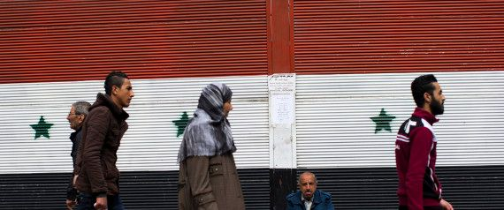 Syrians walk past a shop with a painting of the national flag in Damascus, Syria, Tuesday, Feb. 23, 2016. The Syrian government and the main umbrella for Syrian opposition and rebel groups announced on Tuesday they both conditionally accept a proposed U.S.-Russian cease fire that the international community hopes will bring them back to the negotiating table in Geneva for talks to end the war.(AP Photo/Hassan Ammar)