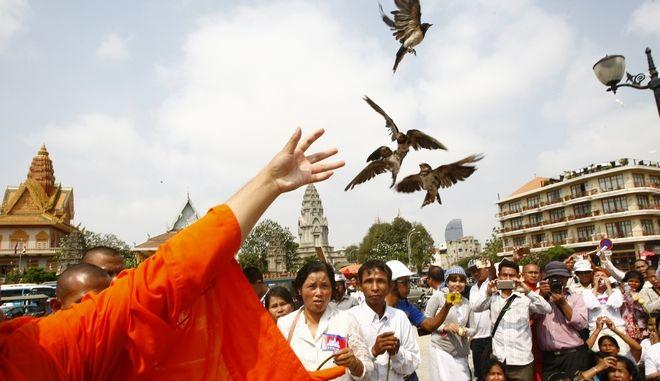 Καμποτζιανοί βουδιστές μοναχοί απελευθερώνουν πουλιά στον ουρανό