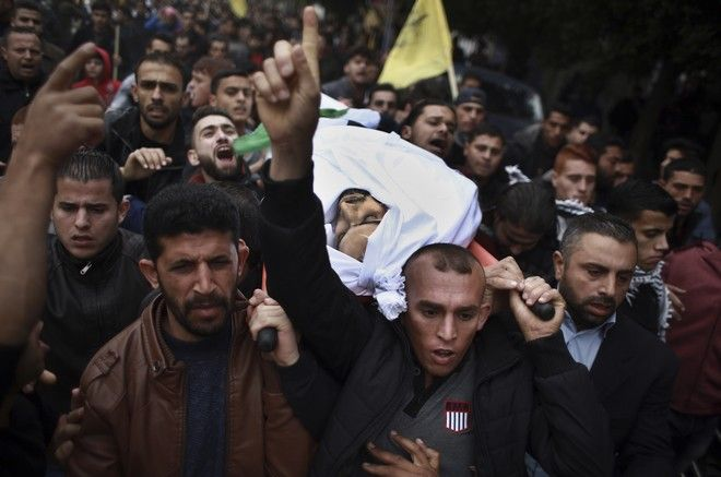 Relatives of Muhammed Muheisen, 28, carry the body out of the family house during his funeral in Gaza City, Saturday, Aug. 23, 2017. Muhieisen was killed in clashes of Palestinians and Israeli troops Friday. (AP Photo/ Khalil Hamra)