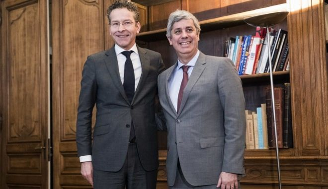 Outgoing leader Jeroen Dijsselbloem, left, of the Netherlands smiles after handing over power of the so-called eurogroup to Portugal's Mario Centeno, right, in Paris, Friday, Jan.12, 2018. The euro zone's new leader says he hopes to use his term to bring the 19 countries that use the currency closer together and toughen their ability to weather future crises. (AP Photo)
