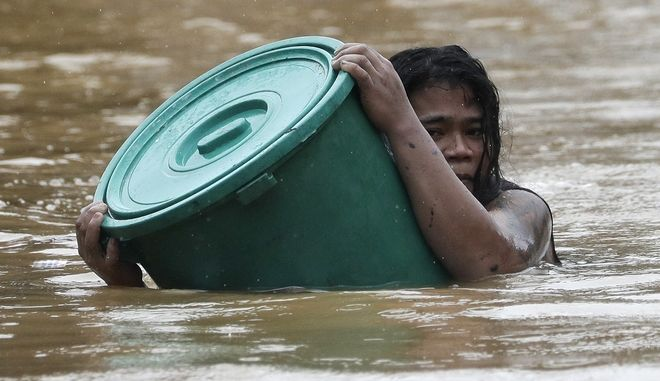 A resident uses a plastic container as a floater while negotiating rising floodwaters in Marikina, Philippines due to Typhoon Vamco on Thursday, Nov. 12, 2020. A typhoon swelled rivers and flooded low-lying areas as it passed over the storm-battered northeast Philippines, where rescuers were deployed early Thursday to help people flee the rising waters.(AP Photo/Aaron Favila)