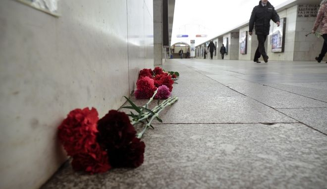 A policeman walks past a flowers at a symbolic memorial at Tekhnologichesky Institute subway station in St. Petersburg, Russia, Tuesday, April 4, 2017. A bomb blast tore through a subway train deep under Russia's second-largest city St. Petersburg Monday, killing several people and wounding many more in a chaotic scene that left victims sprawled on a smoky platform. (AP Photo/Dmitri Lovetsky)