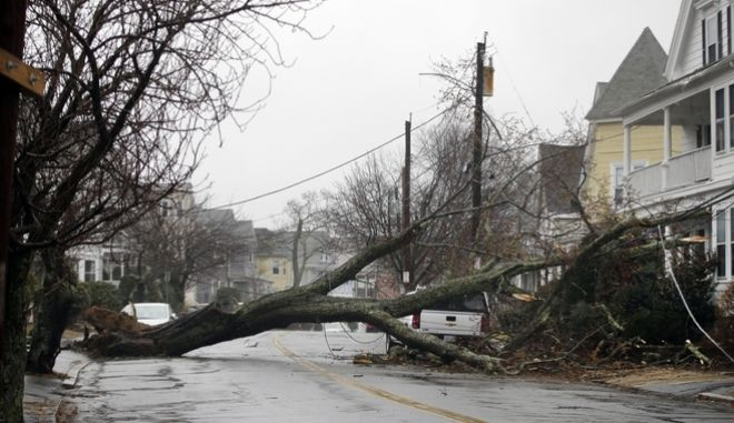 An uprooted tree blocks a residential street after taking down a power line Friday, March 2, 2018 in Swampscott, Mass. as a major nor'easter pounds the East Coast, packing heavy rain, intermittent snow and strong winds. The Eastern Seaboard is expected to be buffeted by wind gusts exceeding 50 mph, with possible hurricane-strength winds of 80 to 90 mph on Cape Cod. (AP Photo/Elise Amendola)