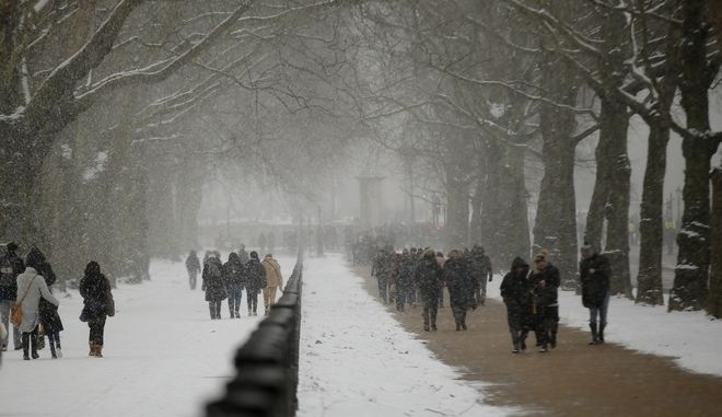 Tourists walk towards Buckingham Palace after overnight snowfalls in London, Wednesday, Feb. 28, 2018. Britain, which is buffered by the Atlantic Ocean and tends to have temperate winters, saw heavy snow in some areas that disrupted road, rail and air travel and forced hundreds of schools to close. (AP Photo/Alastair Grant)