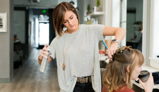 Κομμώτρια φτιάχνει τα μαλλιά σε πελάτισσα