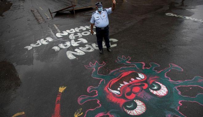 Ινδός αστυνομικός μπροστά από γκράφιτι για τον κορονοϊό