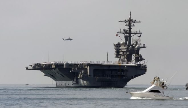 FILE - In this Aug. 22, 2014 file photo, the aircraft carrier USS Carl Vinson sails out of San Diego Harbor leaving for a nine month deployment in San Diego. The U.S. Navy is planning a fresh freedom of navigation operation around Chinas man-made islands, the first under President Donald Trump, Navy Times reported, citing defense officials. The operation would most likely be carried out by the San Diego-based USS Carl Vinson carrier strike group, which began patrolling the South China Sea. It would involve sailing within 12-mile territorial waters of the island features China claims as its own, the report said. (AP Photo/Lenny Ignelzi, File)